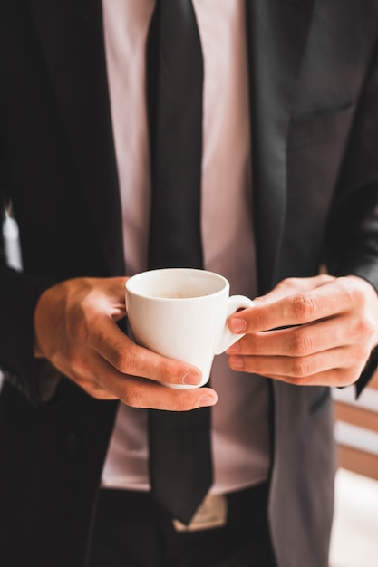 Midsection of businessman holding coffee cup Free Photo