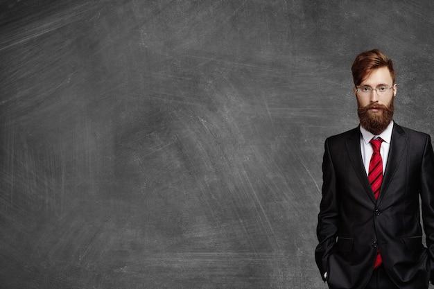 Sezione mediana dell'uomo d'affari con la barba sfocata che indossa un abito nero elegante e occhiali in piedi in ufficio contro la lavagna vuota con lo spazio della copia per il contenuto prima di incontrarsi con i suoi partner Foto Gratuite