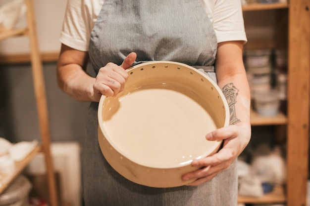 Midsection of a female potter's showing ceramic container in hand Free Photo