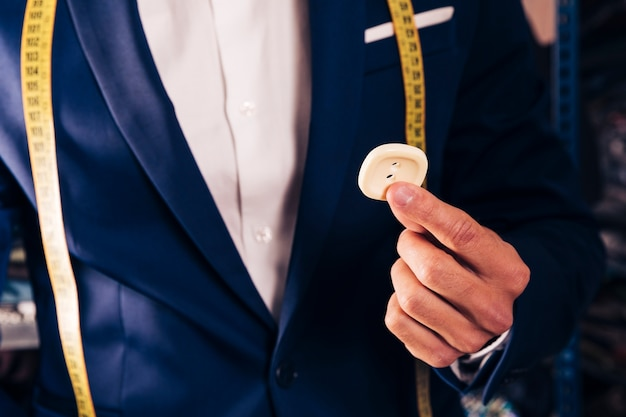 Midsection of a male tailor showing white button Free Photo