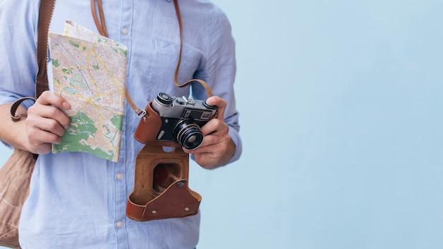 Midsection of male traveler photographer holding camera and map standing against blue background Free Photo