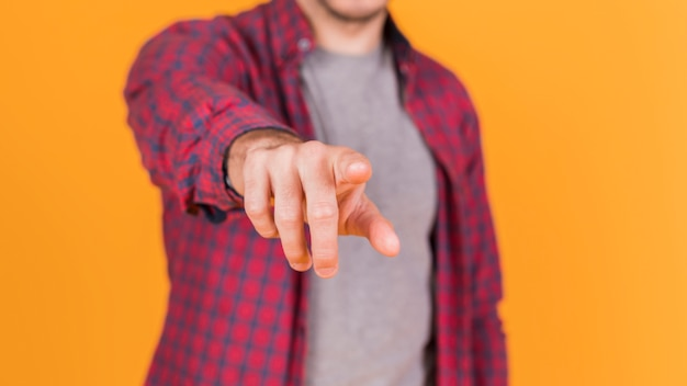 Midsection of a man pointing his finger toward the camera against an orange backdrop Free Photo