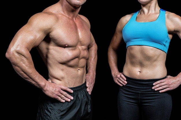 Midsection of muscular man and woman with hands on hip against black background Premium Photo