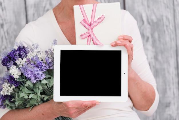 ギフト用の箱を持つ女性の中央部。花の花束と空白の画面デジタルタブレットを手に 無料写真