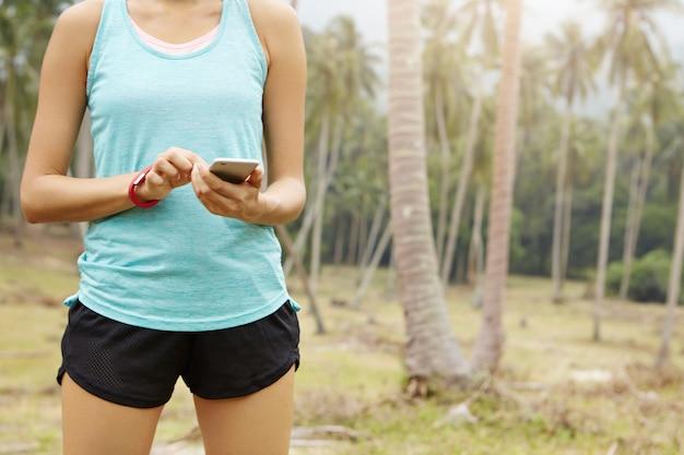 Средняя часть спортивного бегуна вводит данные в приложение для бега на смартфоне, чтобы отслеживать расстояние и время во время бега. Бесплатные Фотографии