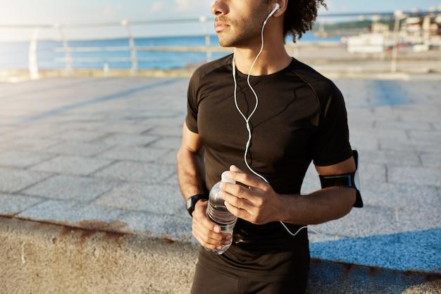 Живот темнокожего бегуна в черной спортивной одежде с бутылкой минеральной воды в руках, использующего музыкальное приложение на мобильном телефоне во время бега за морем. Бесплатные Фотографии
