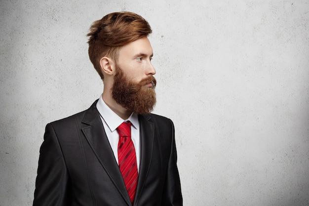 Живот молодого красивого кавказского офисного работника или фрилансера со стильной бородой и стрижкой, одетого в элегантный костюм, смотрящего в пустую стену Бесплатные Фотографии