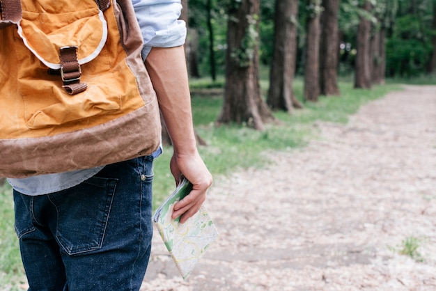 Midsection of traveler man holding map carrying backpack at outdoors Free Photo
