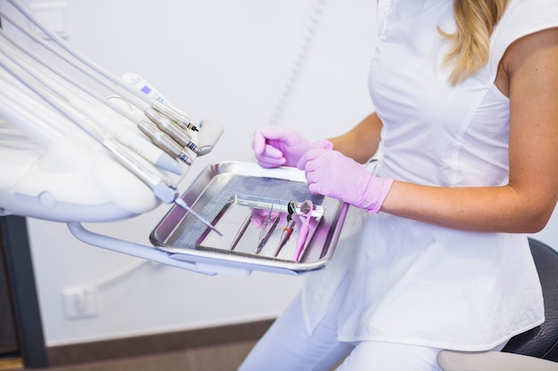 Midsection view of a dentist's hand arranging dental tools on tray Free Photo