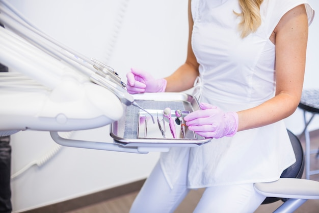 Midsection view of a female dentist with dental tools on tray Free Photo