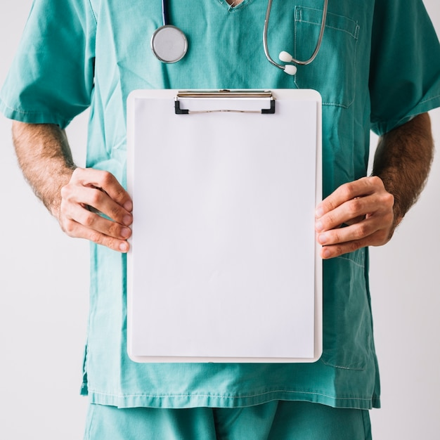 Midsection view of a male doctor holding clipboard with blank white papers Free Photo