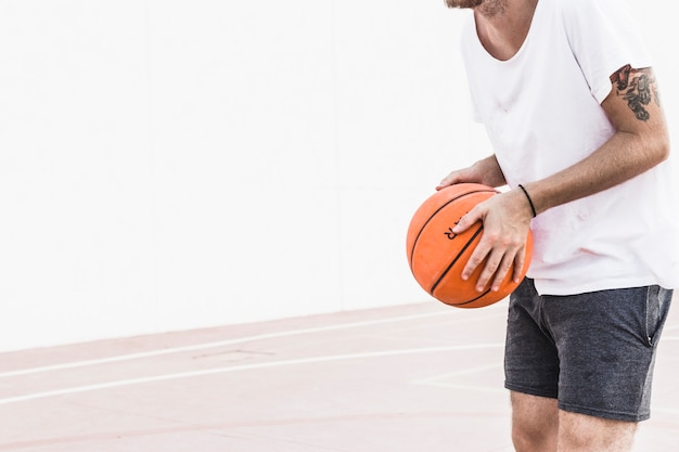 Midsection view of a male player's hand holding basketball Free Photo