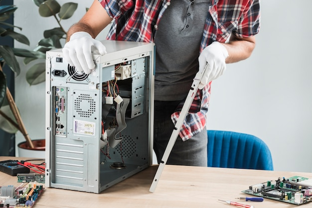 Midsection view of a male technician assembling computer on wooden desk Free Photo