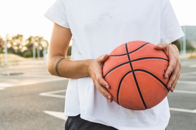 Midsection view of a man holding basketball Free Photo