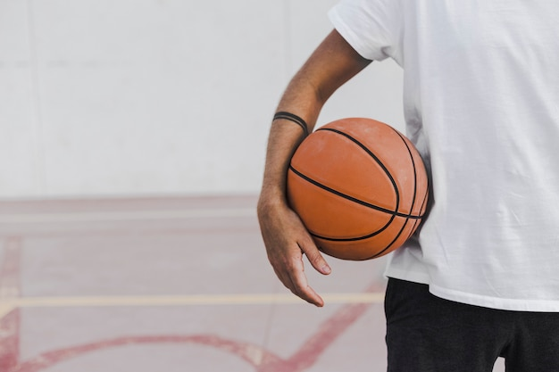 Midsection view of a man's hand with basketball Free Photo