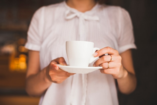 Midsection of woman holding coffee cup while standing in restaurant Free Photo