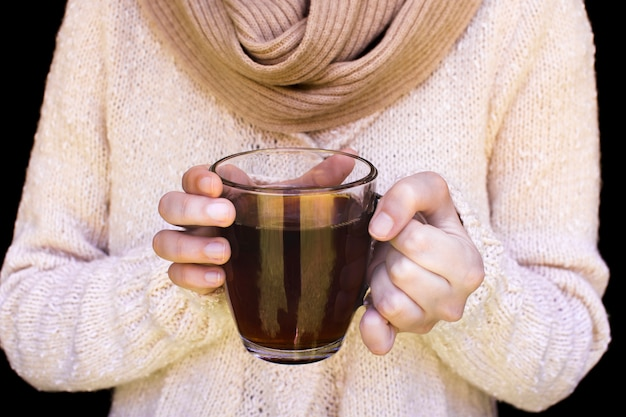 Midsection of a woman wearing woolen sweater holding glass cup of herbal tea Free Photo