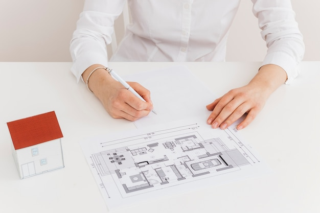 Midsection of woman working on house blueprint at desk in office Free Photo