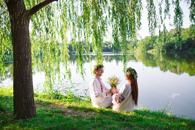 Midsummer. young loving couple in slavic costumes on the shore of the lake. slavonic holiday of ivan kupala. Premium Photo