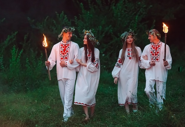 Midsummer, young people in the same slavic costumes are holding torches with fire. Premium Photo