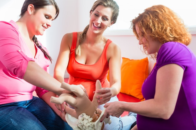 Midwife explaining birth process to pregnant women during antenatal class Premium Photo