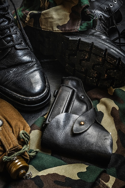 Military camouflage uniform and boots. a set of military items flask gun on a dark background Premium Photo