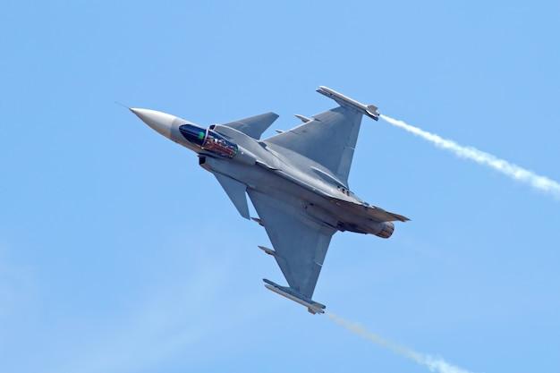 Military fighter jet on blue sky Premium Photo
