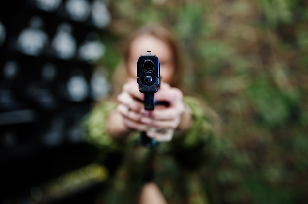 Military girl in camouflage uniform with gun at hand against army background on shooting range. focus on gun. Premium Photo