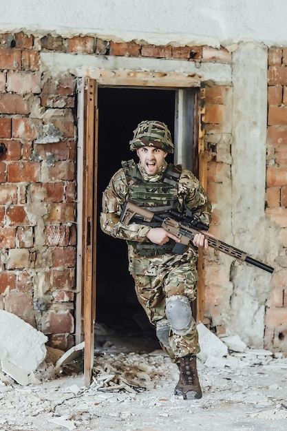 Military runs out of the door and holds a big rifle! fighting in a destroyed building Premium Photo