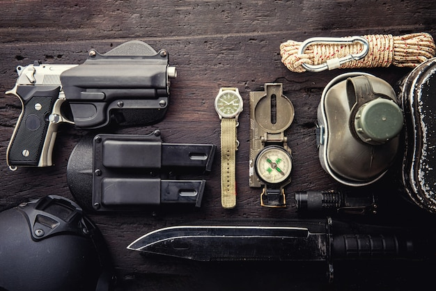 Military tactical equipment for the departure. assortment of survival hiking gear on wooden background Premium Photo