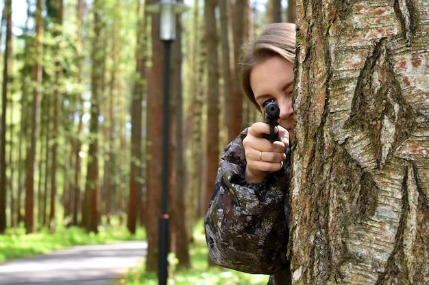 Военная женщина стреляет из ружья в лесу. девушка-охотник прячется за деревом с оружием. Premium Фотографии