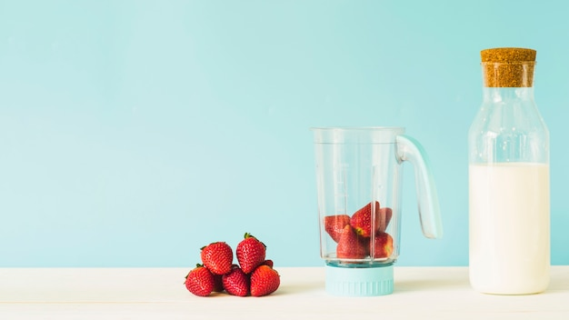 Milk bottle near strawberry in blender on wooden table Free Photo