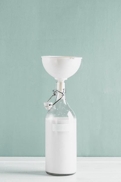 Milk bottle with funnel Free Photo