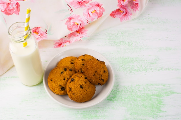 Milk bottle with straw and cookies Premium Photo