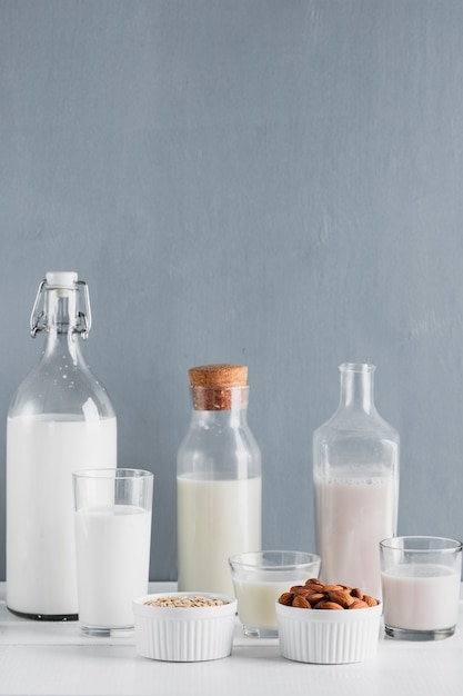 Milk in bottles and glasses with oats and almonds Free Photo