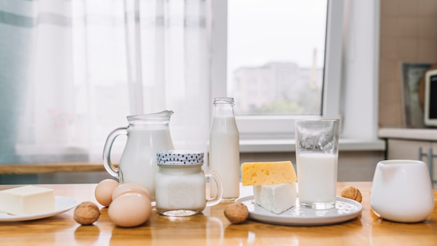 Milk; cheese; eggs and nuts on a wooden table in kitchen Free Photo