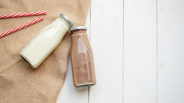 Milk and chocolate milk on a white wooden table. Premium Photo