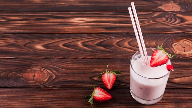 Milk cocktail with strawberry on wooden surface Free Photo