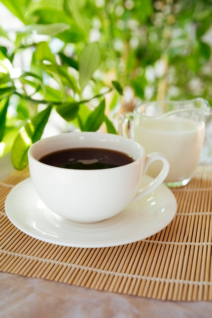 Milk and coffee cup on bamboo mat Free Photo