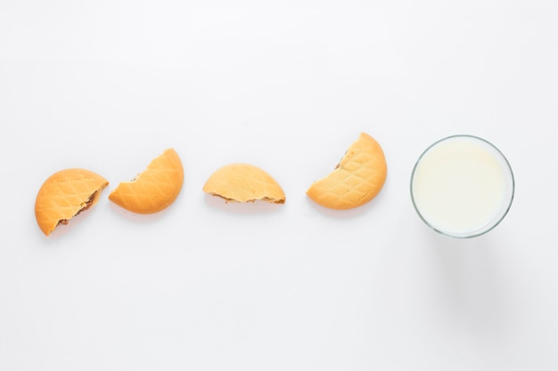 Milk and cookies arranged in a row for morning breakfast over white background Free Photo