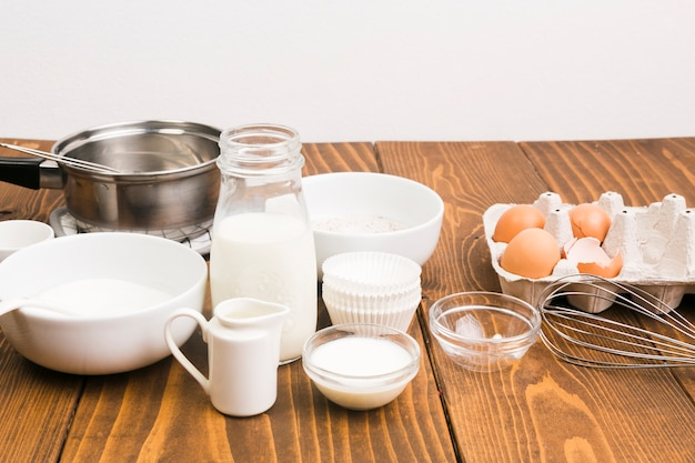 Milk; egg; and cooking utensils on kitchen counter Free Photo