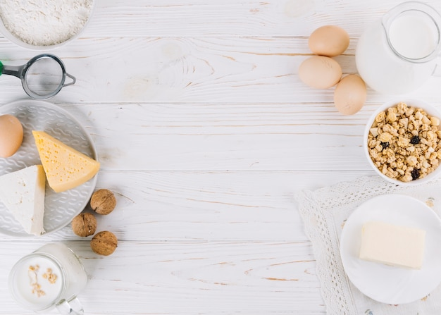 Milk; eggs; bowl of cereals; cheese; flour and walnuts on white wooden table Free Photo
