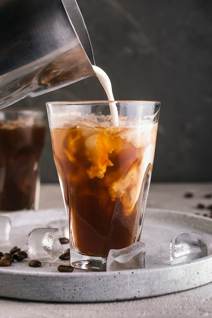Milk pouring into glass with coffee Free Photo