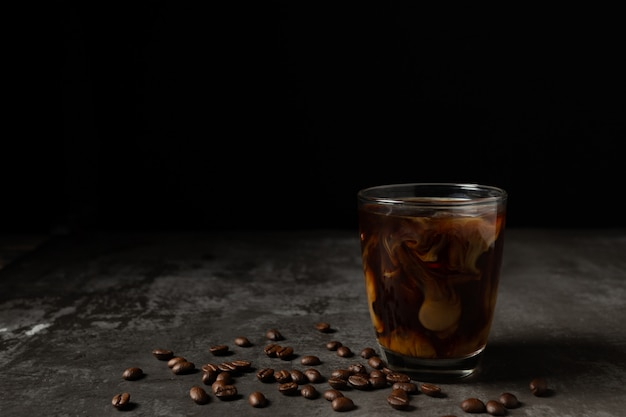 Milk pouring into iced black coffee on table Free Photo