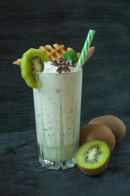 Milk shake with kiwi, ice cream and whipped cream, marshmallows, cookies, waffles, served in a glass cup. Premium Photo
