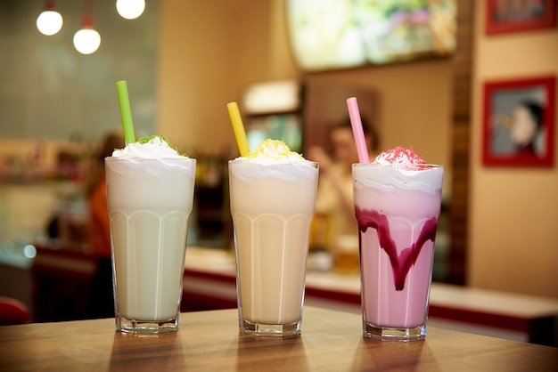 Milk shakes with straws on a wooden table in a cafe. Premium Photo