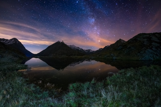 The milky way arc and the starry sky reflected on lake at high altitude on the alps. Premium Photo