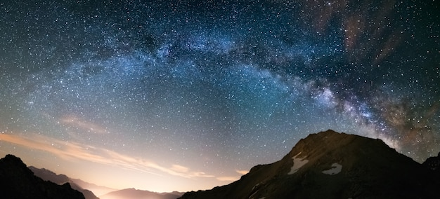Milky way arch and starry sky on the alps. panoramic view, astro photography, stargazing. light pollution in the valley below. Premium Photo