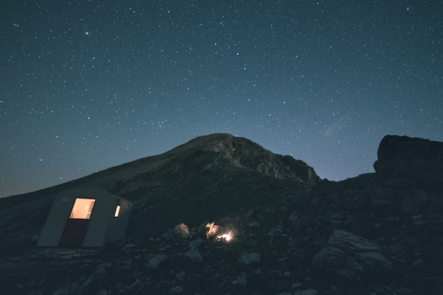 The milky way over the mountains, long exposure on the italian-french alps, mountain hut and refuge illuminated. toned image, vintage filter, split toning. Premium Photo