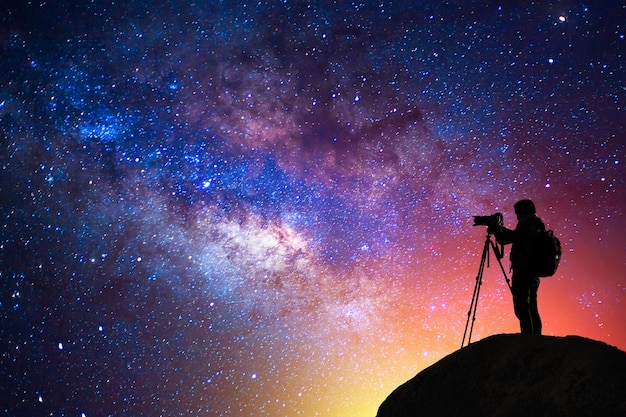 Milky way, star, silhouette happy camera man on the mountain with detail of the milky way Premium Photo